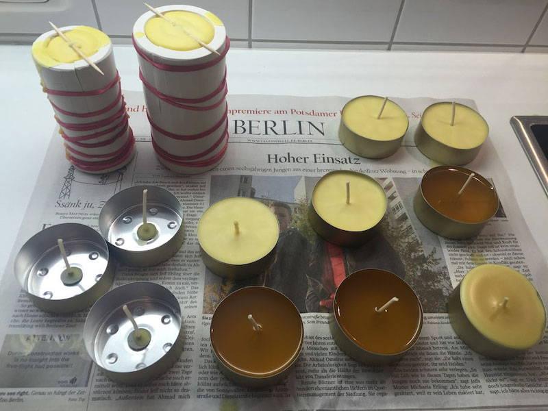 Bienenwachskerzen stehen auf einer Seite Zeitungspapier zum abkühlen