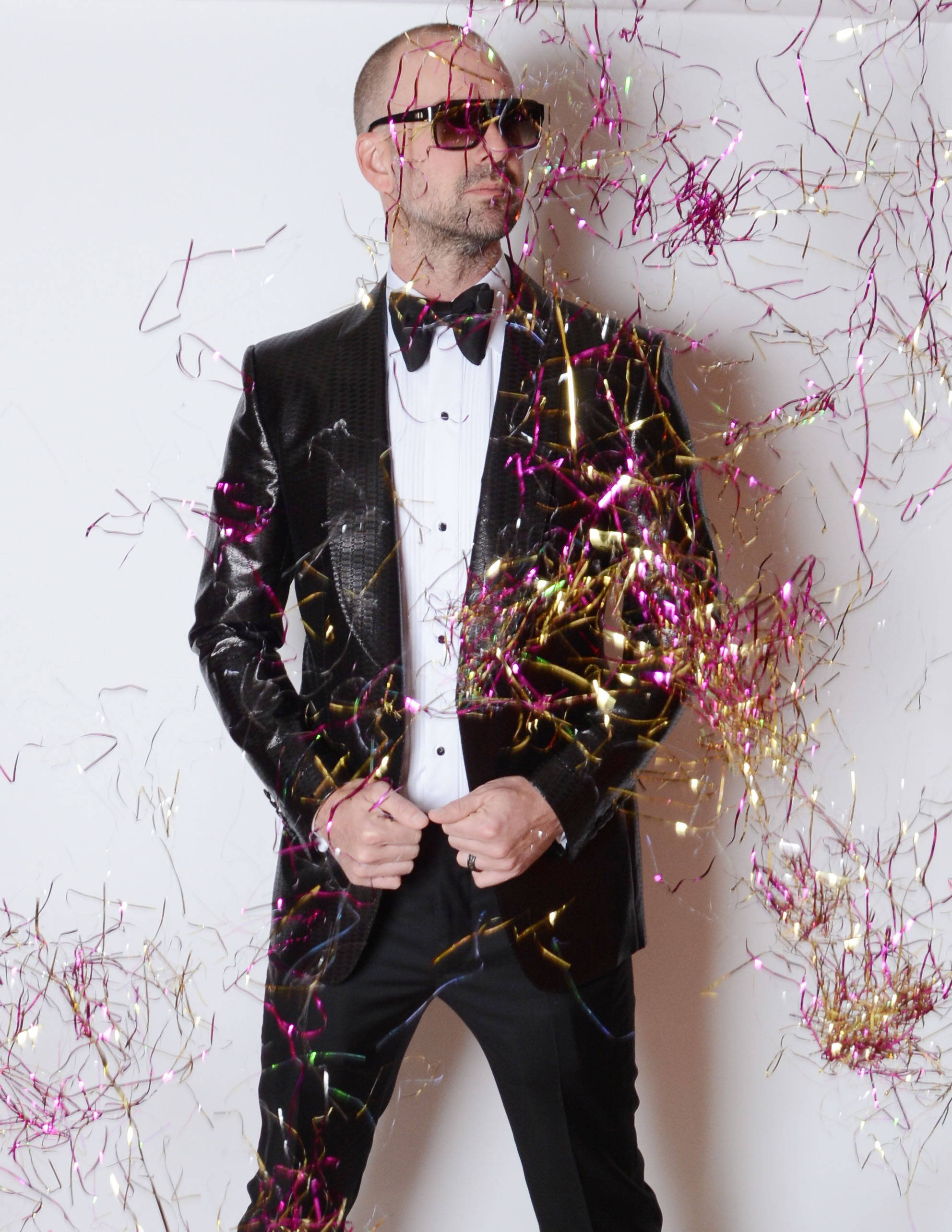 Dr. Barczak in a black tux and sunglasses with confetti dropping down on him