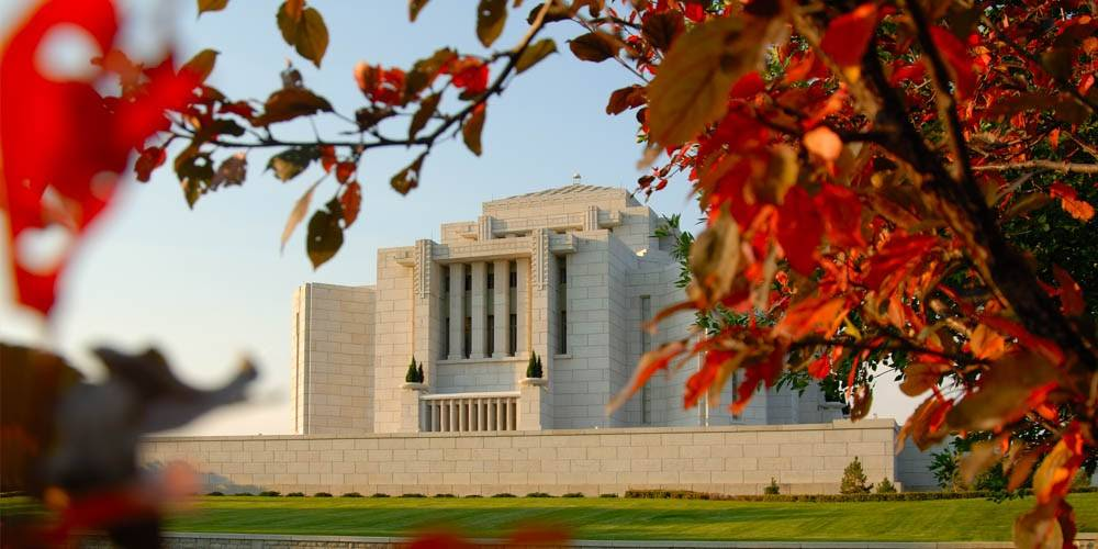 Cardston LDS Temple framed by autumn leaves.
