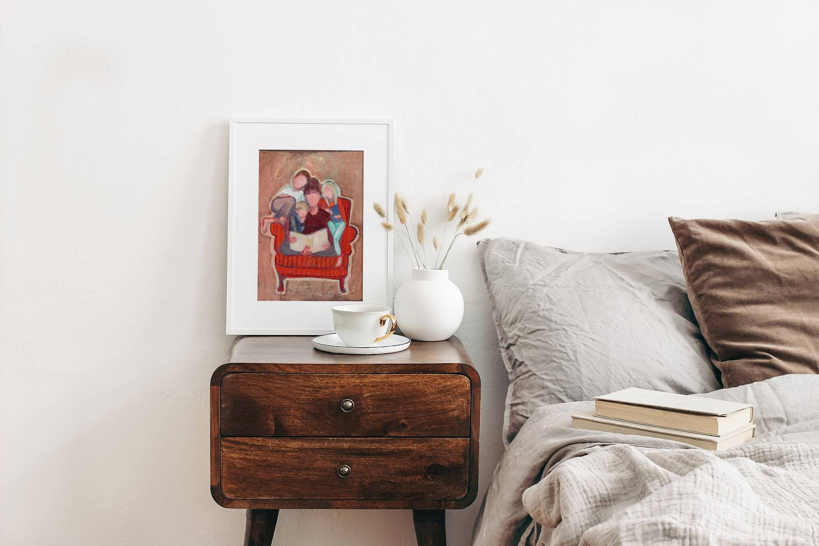 Small wall art of mother reading to her children. Painting is placed on a small end table among small glass items and is leaning against the wall.