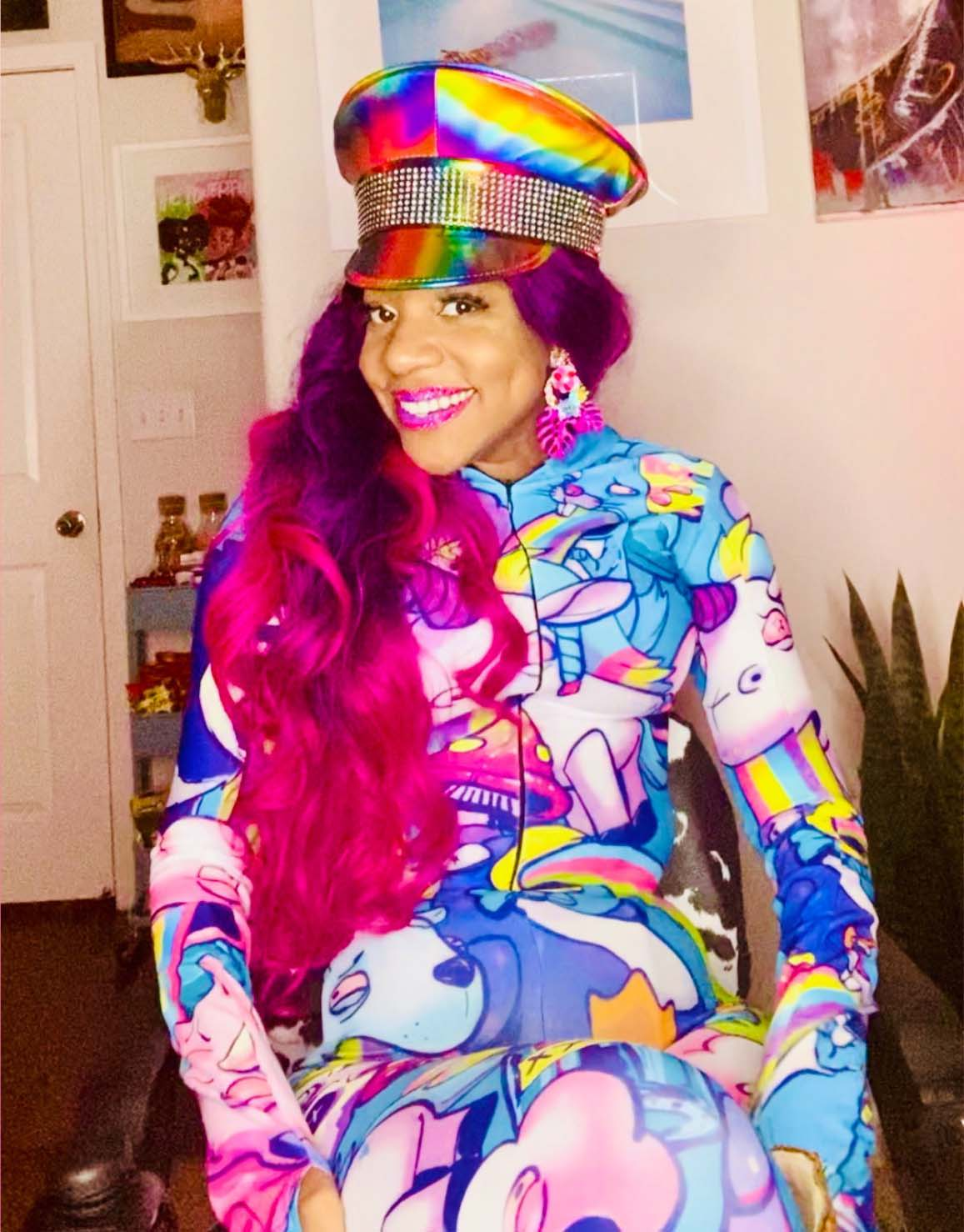 Krystina Jackson, Ms. Wheelchair CA 2018 and LGBTQ+ Advocate, smiles at the camera wearing a rainbow onesie.