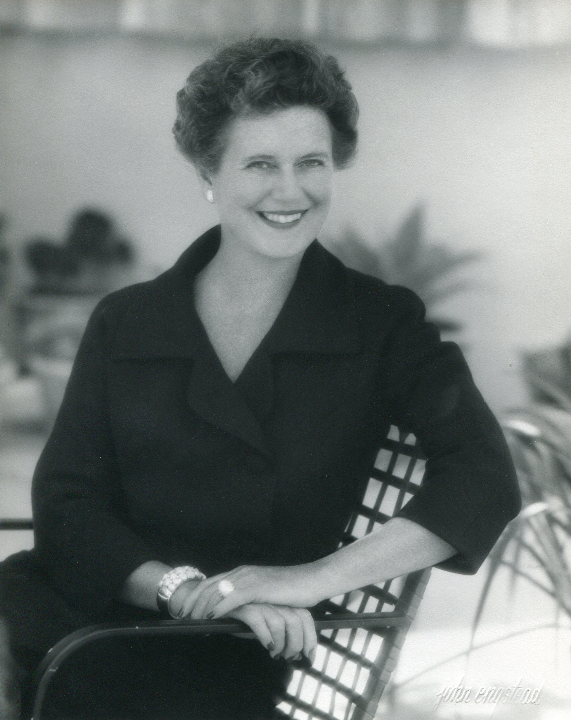 A black and white portrait of Dorothy Chandler seated outdoors, smiling at the camera.