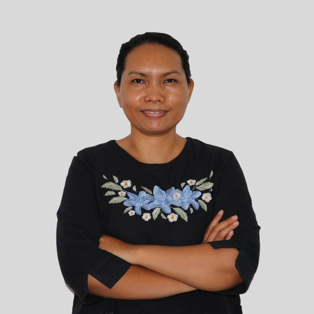 Indonesian woman in black top with blue embroidered front arms folded smiling with pulled back hair
