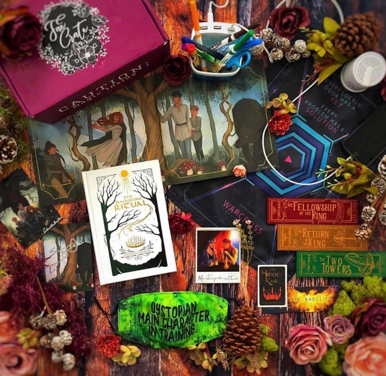 September 2020 Alliance box theme includes The Blackstone Ritual by Swearingen Durham, WHTF Polaroid, Dystopian MC in Training Face Mask, LOTR Felt Bookmar Set, Red Rising Bucket Organizer Light, Stolen Songbird Speaker, Warcross Wall Hanging, A Song Below Water Olympian Art Print, and Iron Fey Shirt.