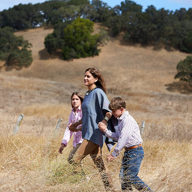 Elizabeth and her children walk across an open field on a sunny day.