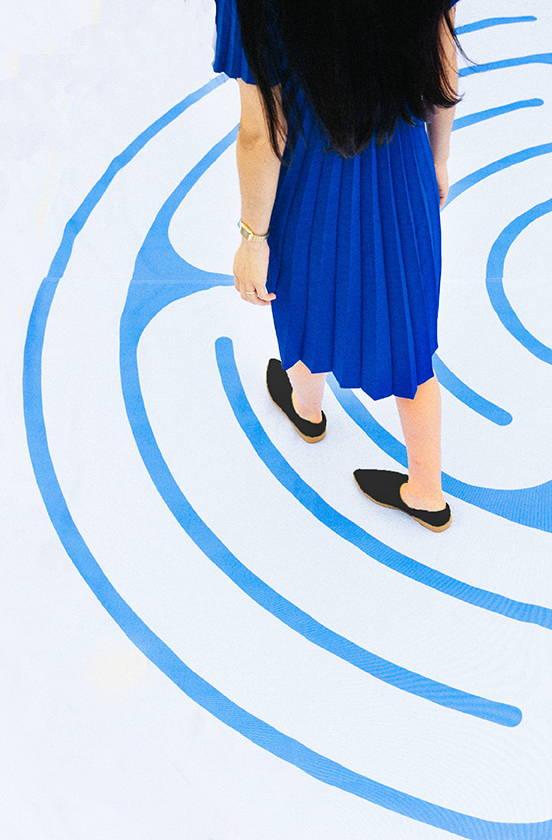 Girl in blue dress walking away wearing black VQS shoes