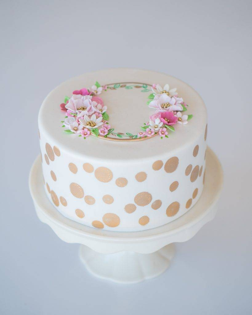 Birthday cake with a circle of flowers on top and gold polka dots