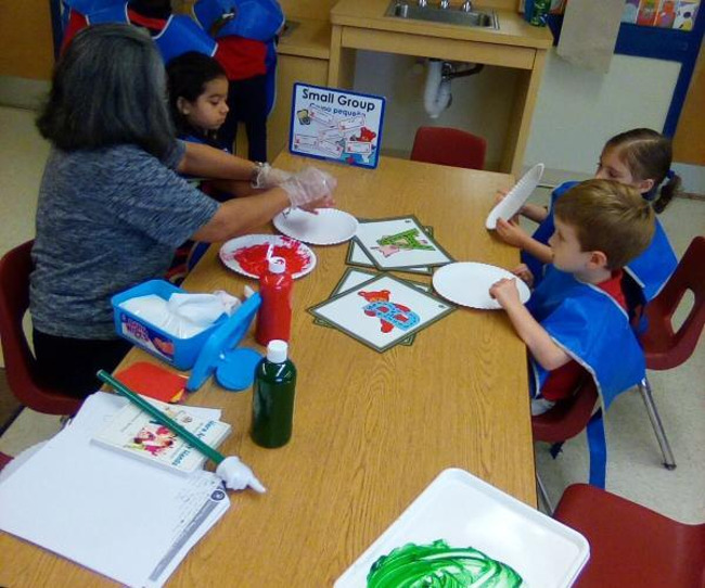 Students wearing smocks with one being helped by the teacher to make a handprint using paint on a paper plate