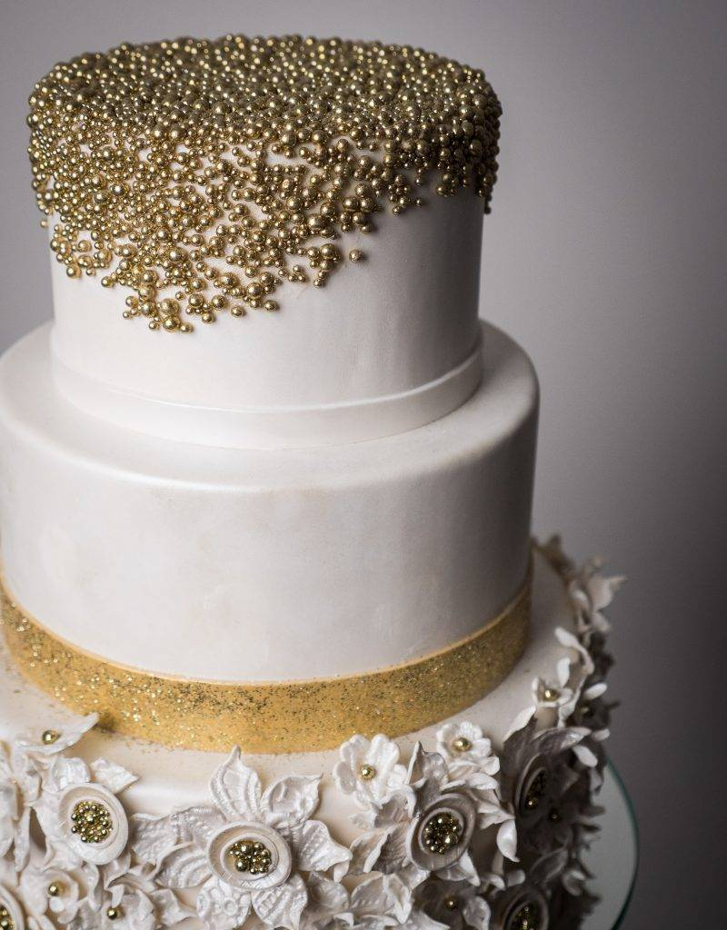 Wedding cake with gold pearl details and gold flowers