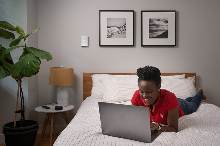 woman smiling and laying on her bed while on her laptop