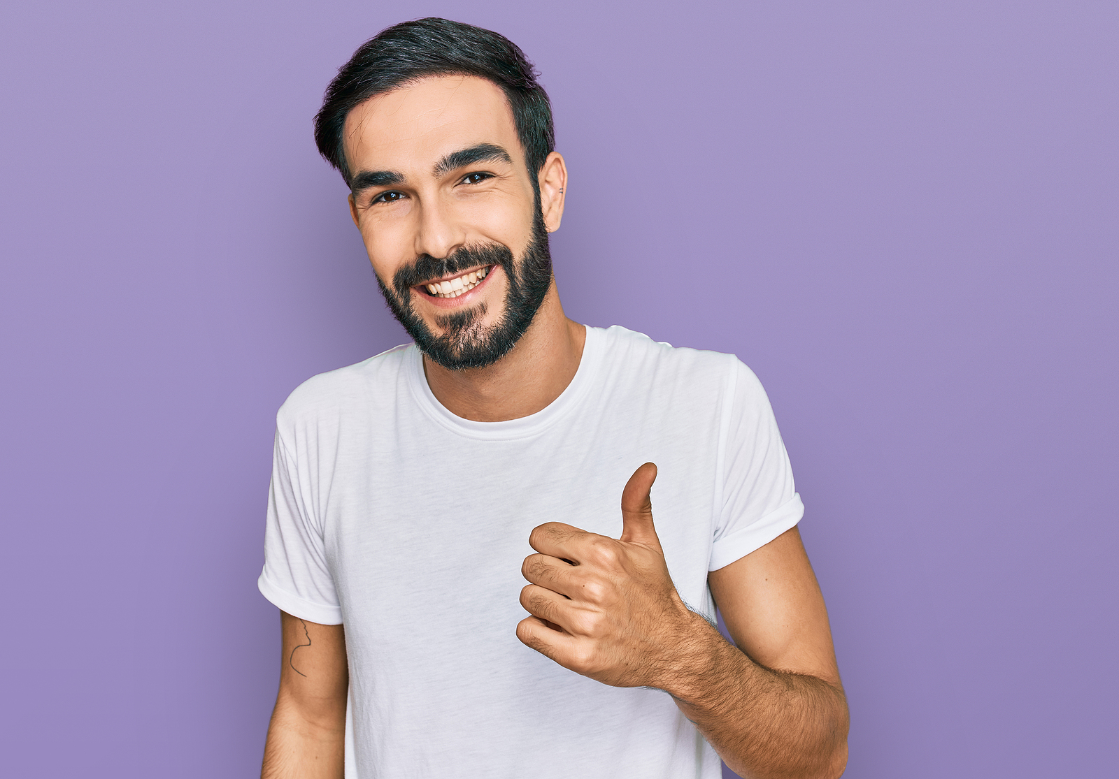 Picture of a man smiling with a beard and a white t shirt with thumbs up on purple background.