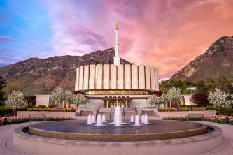 Provo Temple against an orange and blue sky.