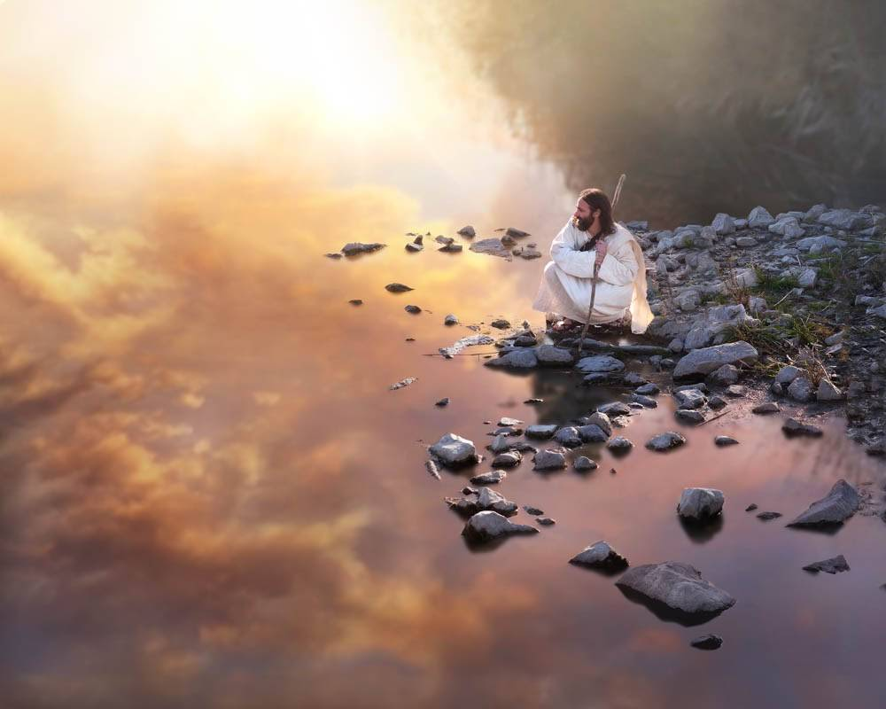 Image of Jesus crouched on the shore of a lake. The water reflects a pink, purple, and golden sky.