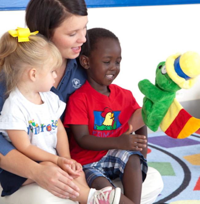 A preschool teacher and young children at school