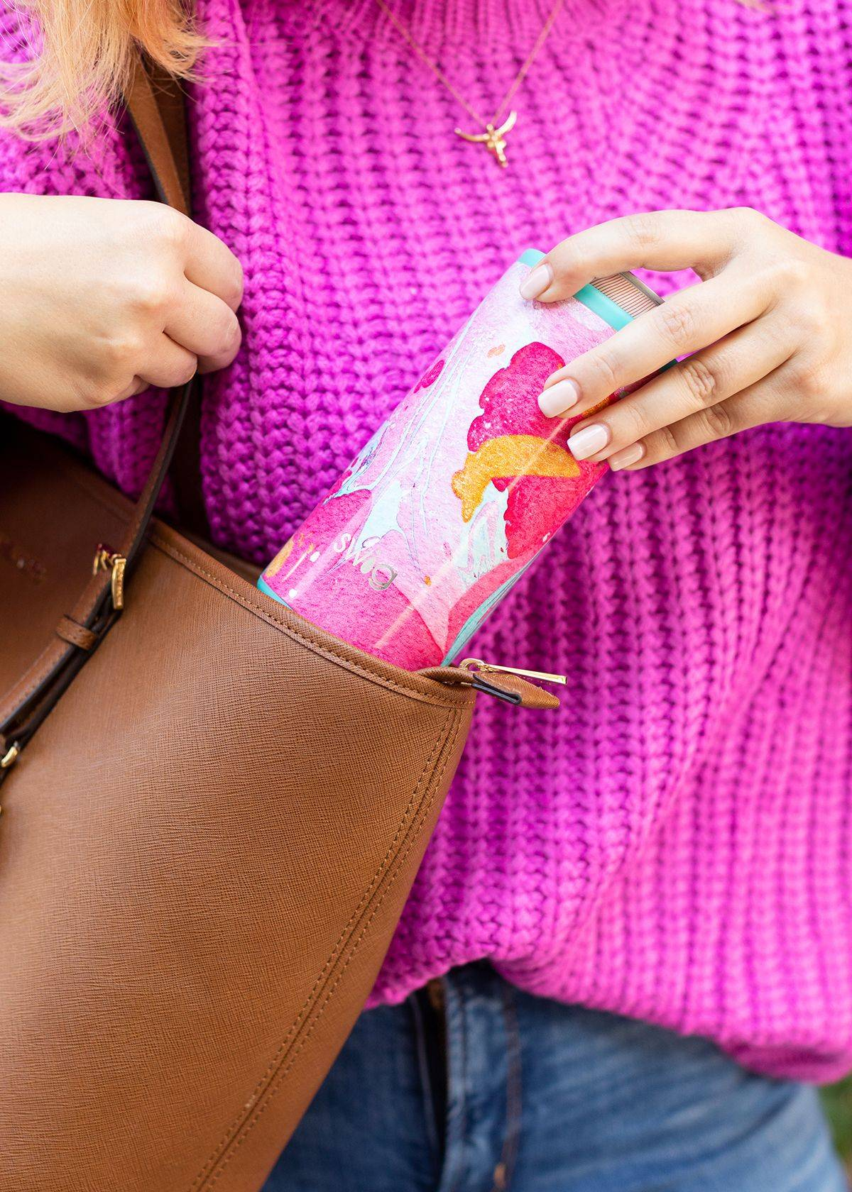 A woman putting her swig in her handbag
