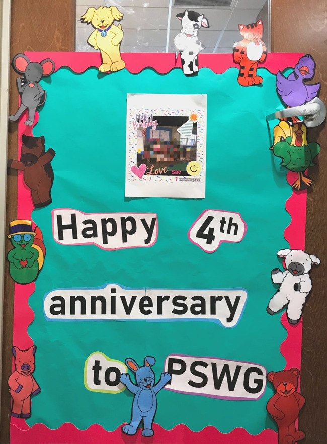 """Classroom door decorated with Primrose puppet characters that says """"Happy 4th anniversary PSWG!"""""""