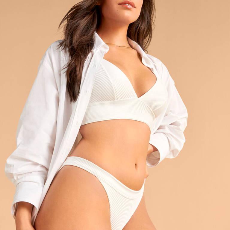 brunette women in white clothing against tan background