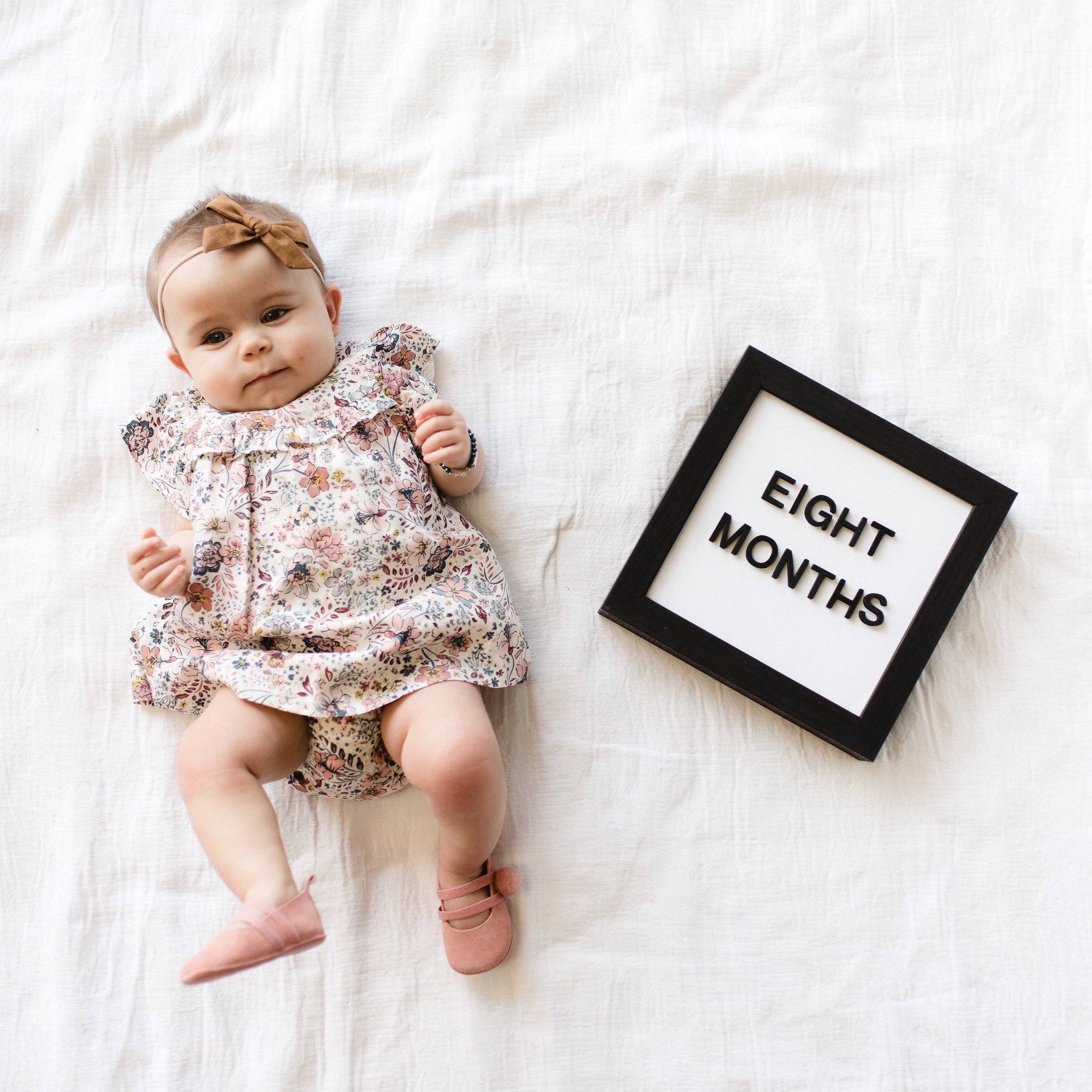 baby laying next to magnetic letter board