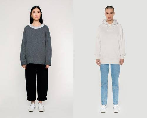 Woman wears organic cotton grey wide scoop neck jumper with rolled up wide leg black trousers and woman wears cream hoodie with light wash jeans, both from sustainable fashion brand Rotholz