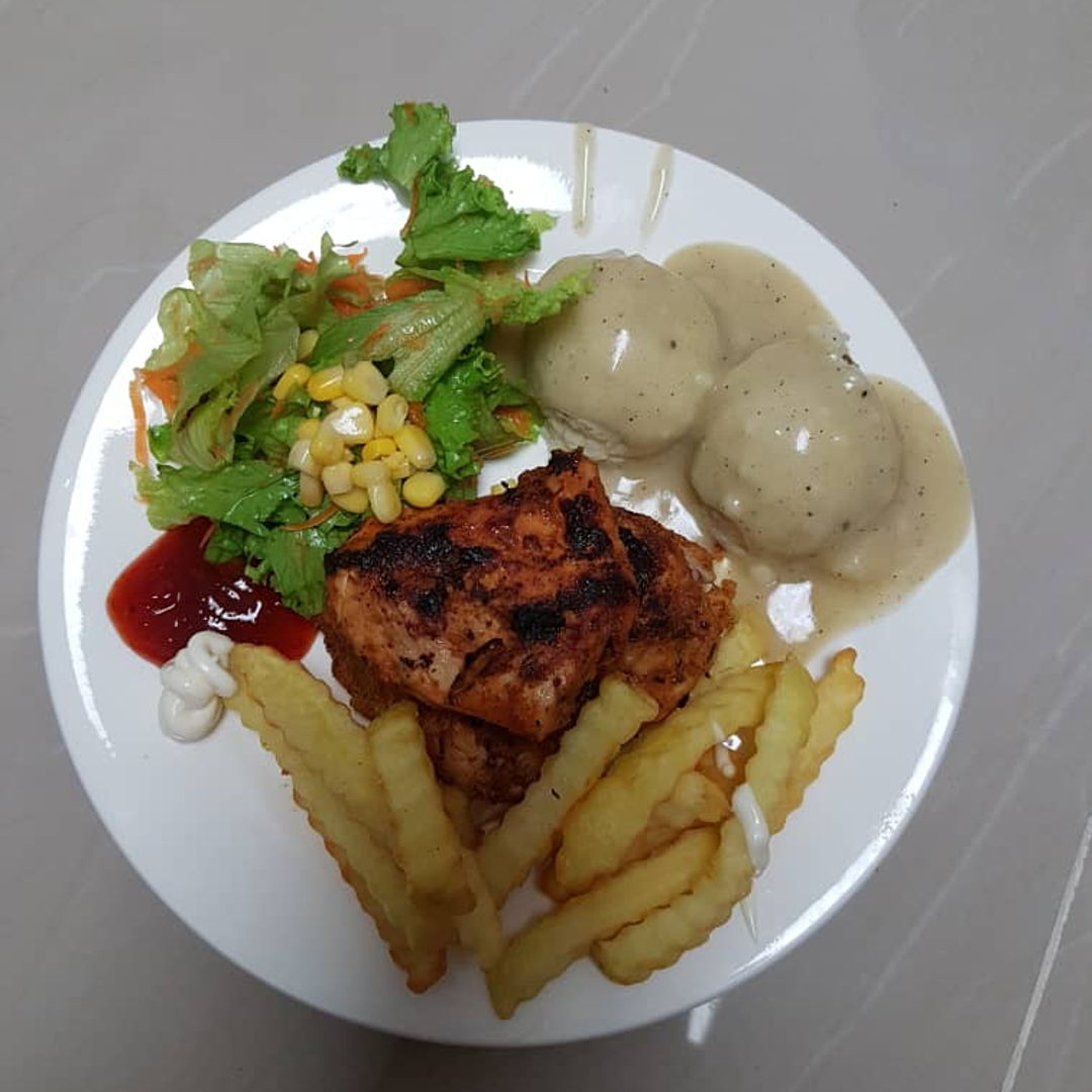 Grilled chicken with homemade mashed potato, brown sauce and vegetables salad and some French fries..
