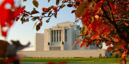 Cardston Temple framed by red leaves.