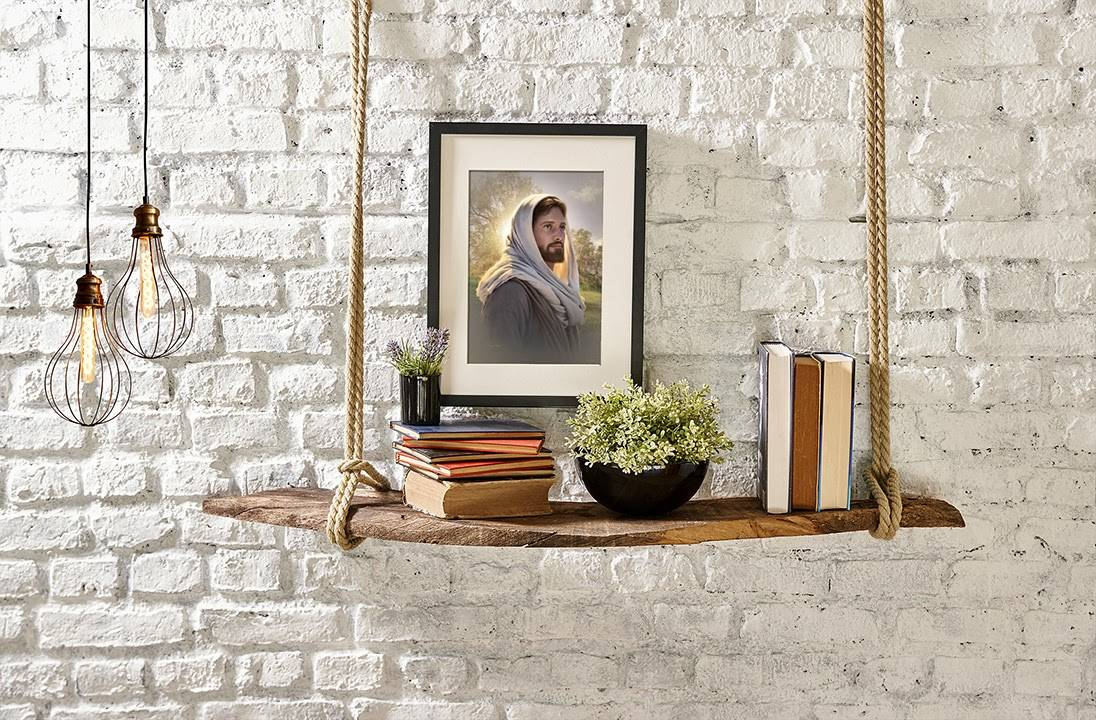 Small art portrait of Jesus hanging on a brick wall above a hanging shelf of books.