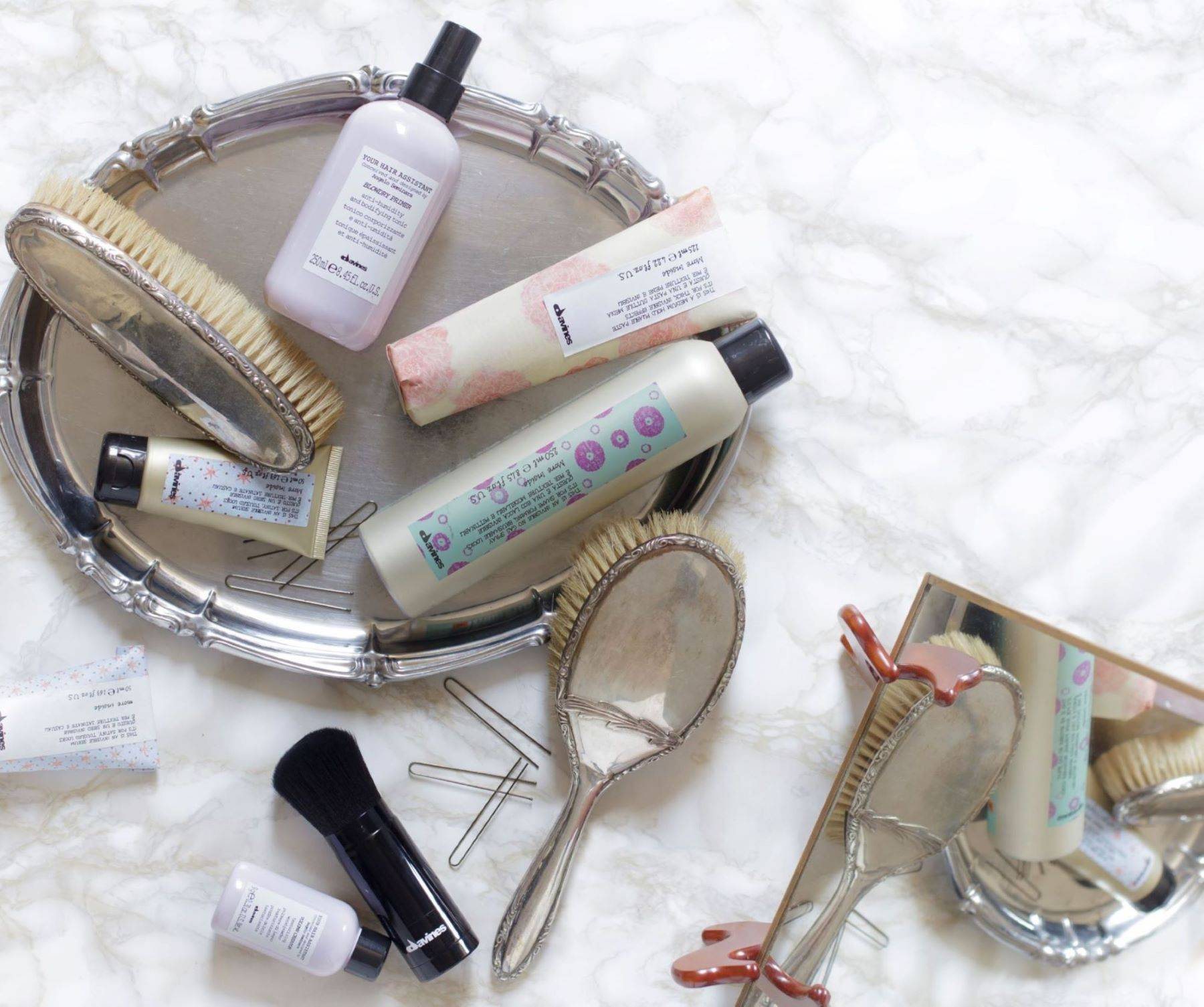 Davines products laying on a marble surface with a tray, hair brush, and styling tools