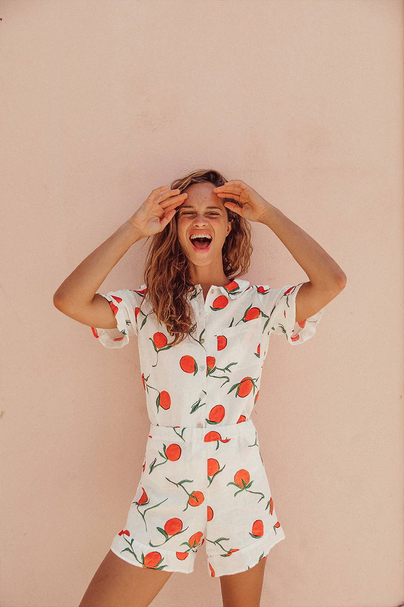 Woman standing against a peace coloured wall wearing YOLKE Orange Thebe Short set featuring printed oranges on linen