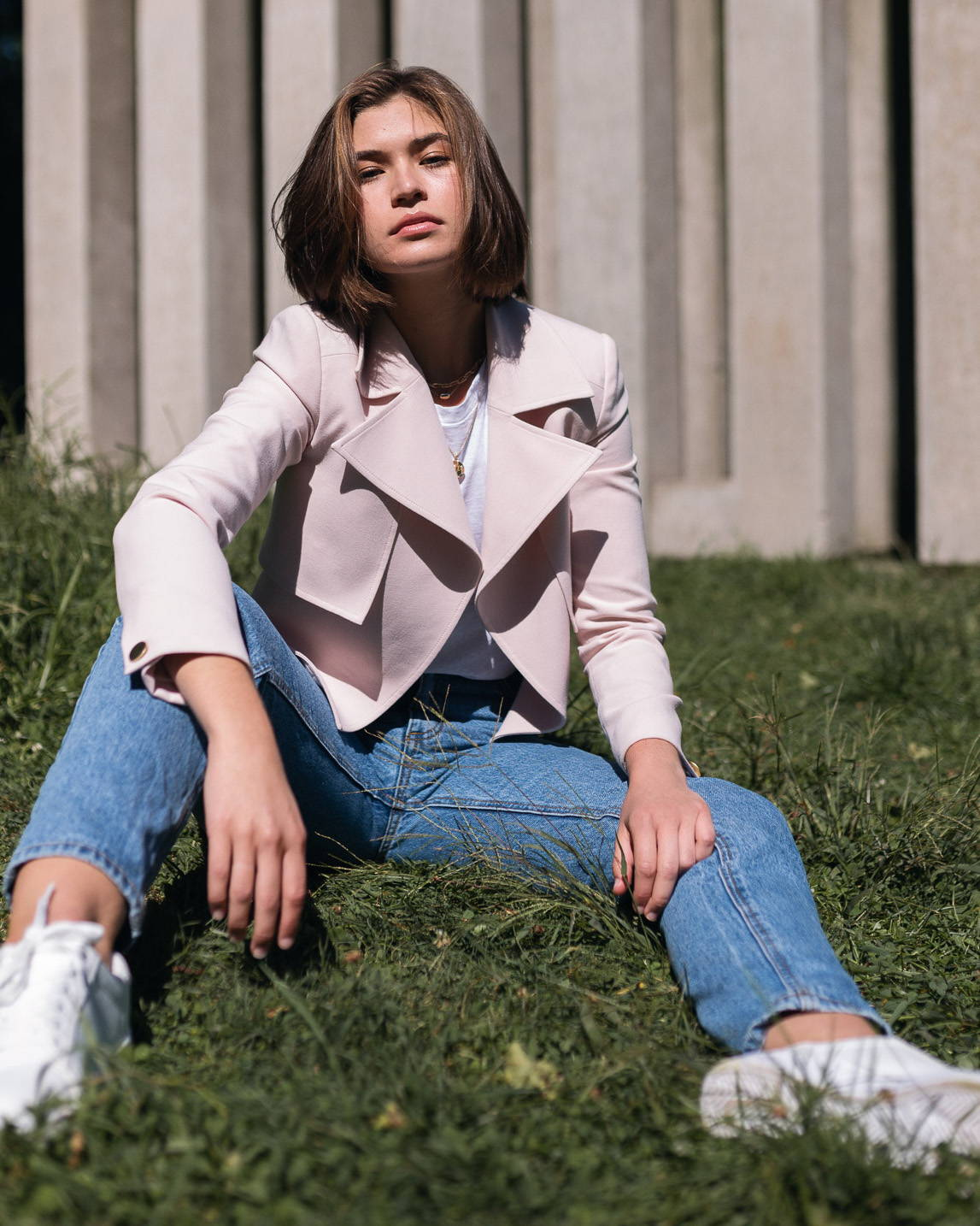 ixora apparel model sitting in grass  wearing pink cropped trench jacket aline