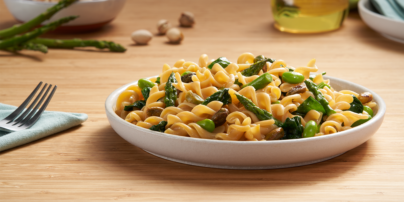 A bowl of ZENB Rotini Pasta with asparagus, mushrooms and peas