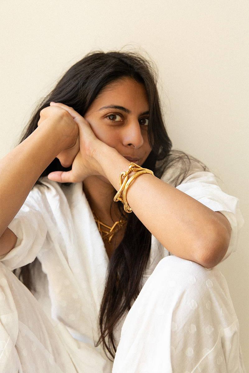 Rosh Mahtani smiles at the camera in YOLKE's Jacquard White Cotton Classic Pyjamas and Alighieri Jewellery