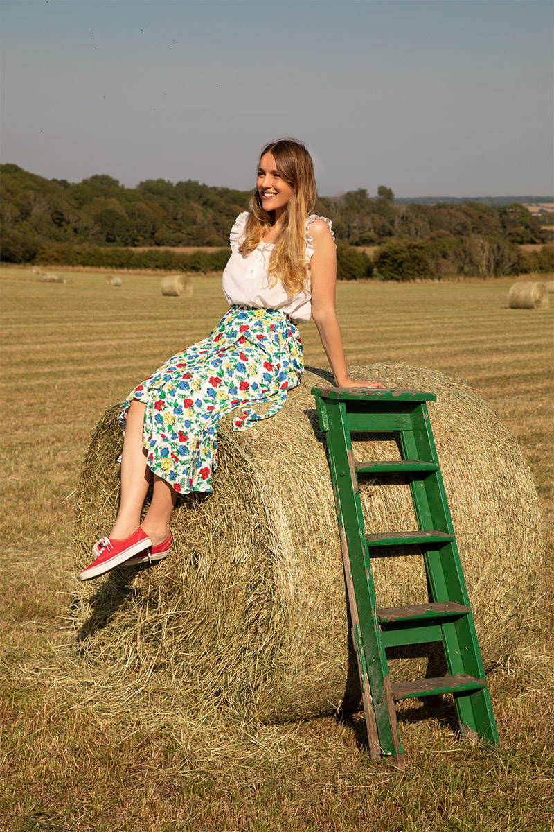Tess Newall perches on a hay bale whilst wearing YOLKE