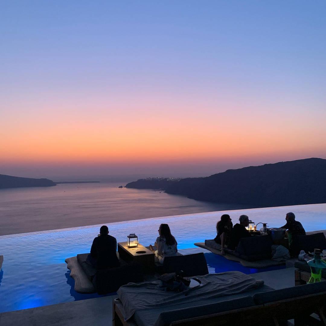 Cavotagoo infinity pool overlooking Santorini caldera at sunset