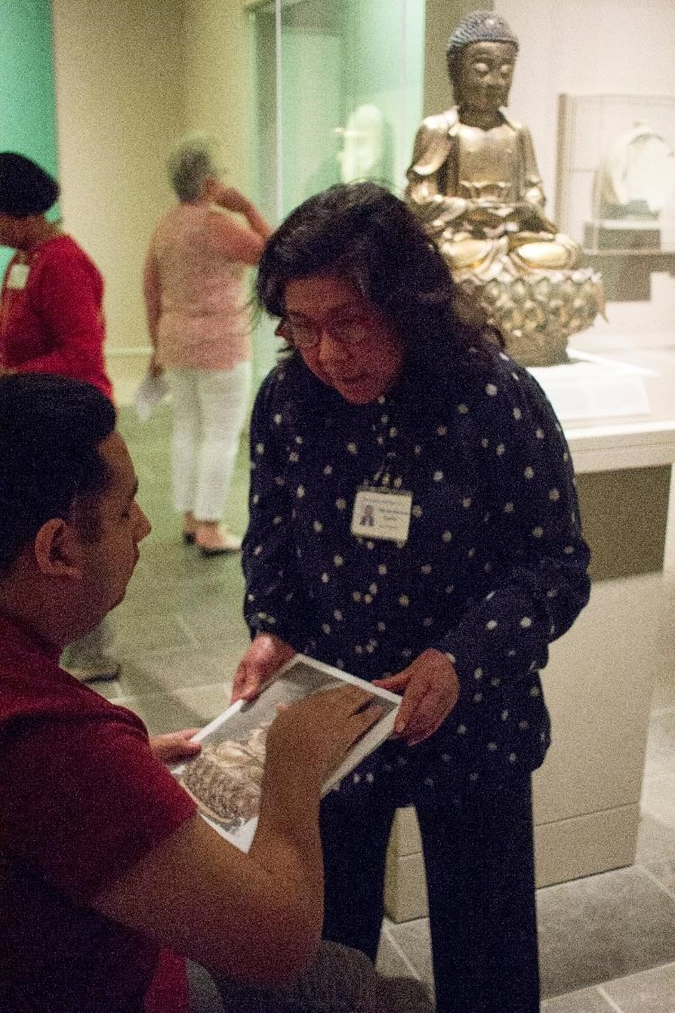 A museum docent shares a tactile model of an artwork through touch with a visitor