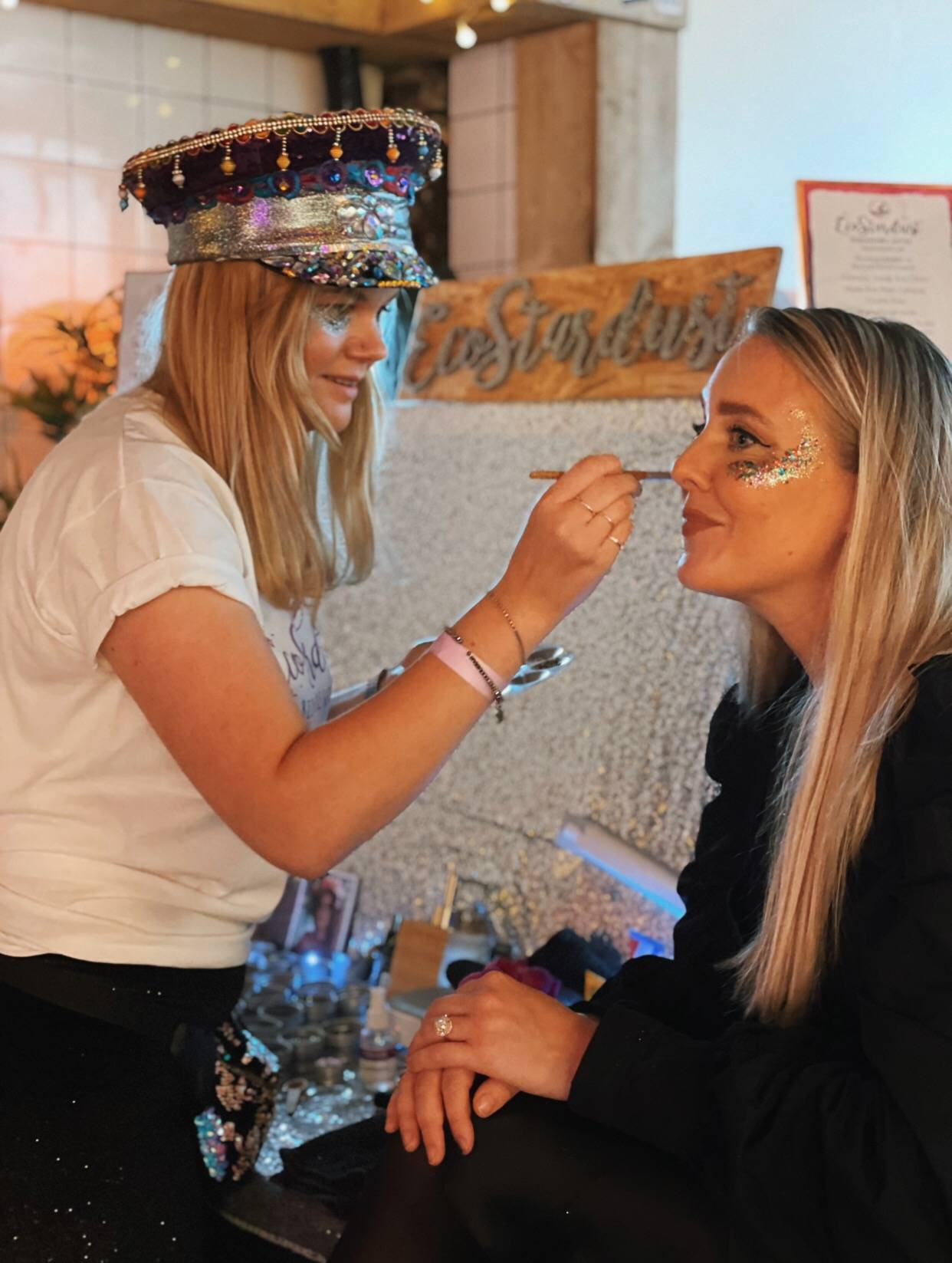 Image shows our founder Kath glittering someone at the biodegradable glitter bar. The woman already has lots of glitter on her face, and Kath is holding a bamboo makeup brush up to her face. They're both smiling.