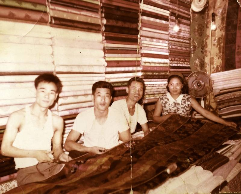 LEEHWA HISTORY. GROUP OF PEOPLE SITTING WITH FABRICS.