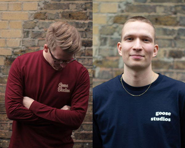 Man wearing organic cotton navy blue organic cotton t-shirt with Goose Studios text logo on left chest and man wearing burgundy organic cotton long sleeve t-shirt with Goose Studios logo, both from sustainable fashion brand Goose Studios