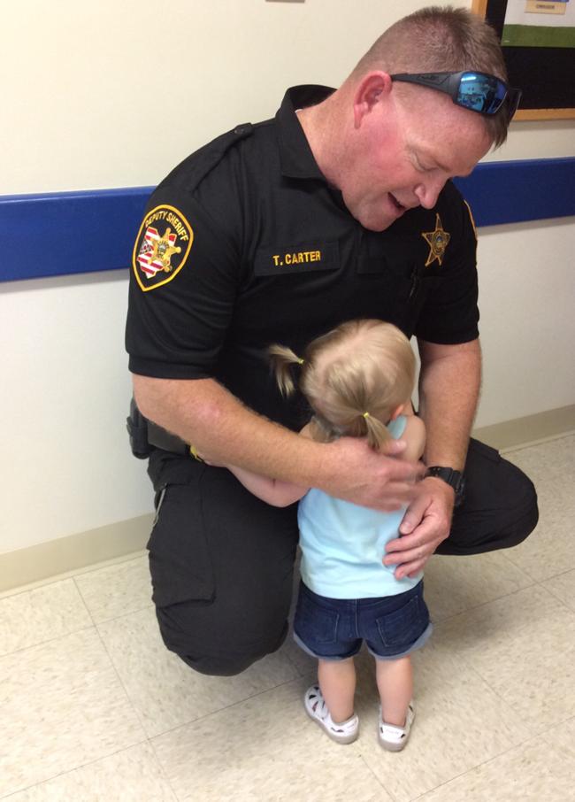 Little girl hugging the sheriff