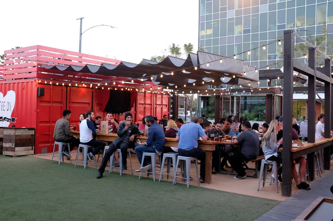 wide angle view of our SteelCraft locatio in long beach, people can be seen on stools enjoying food and beer.