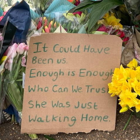 Flowers and placard for Sarah Everard at Clapham Common bandstand