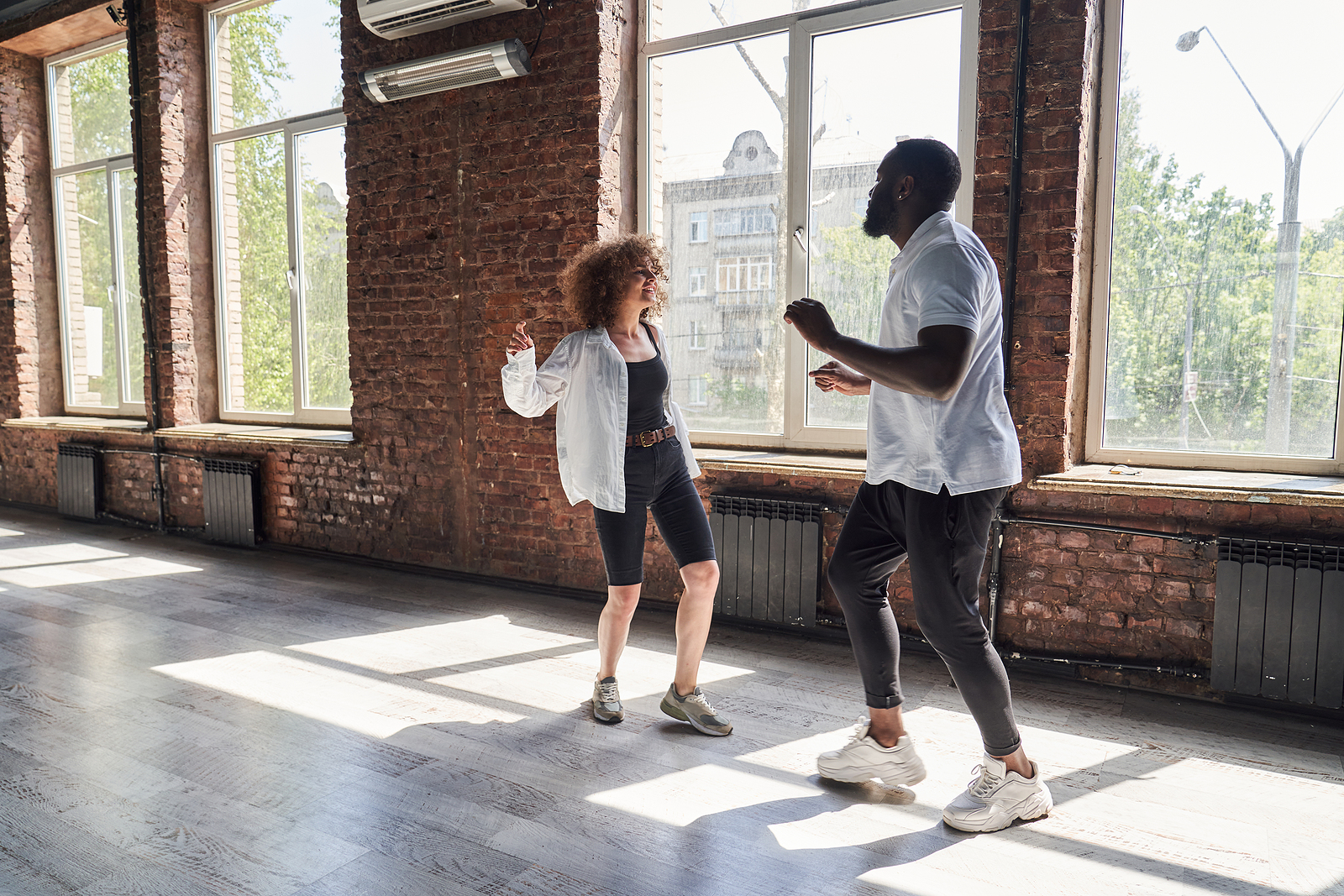 Photo of young hip black couple inside a brick room with open windows dancing together smiling.