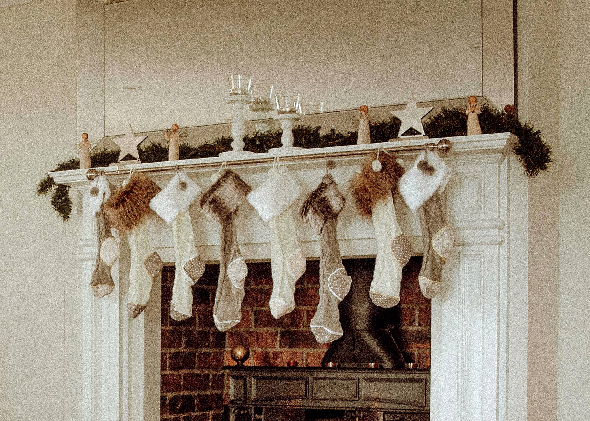 Display of stockings hanging in front of a fire place