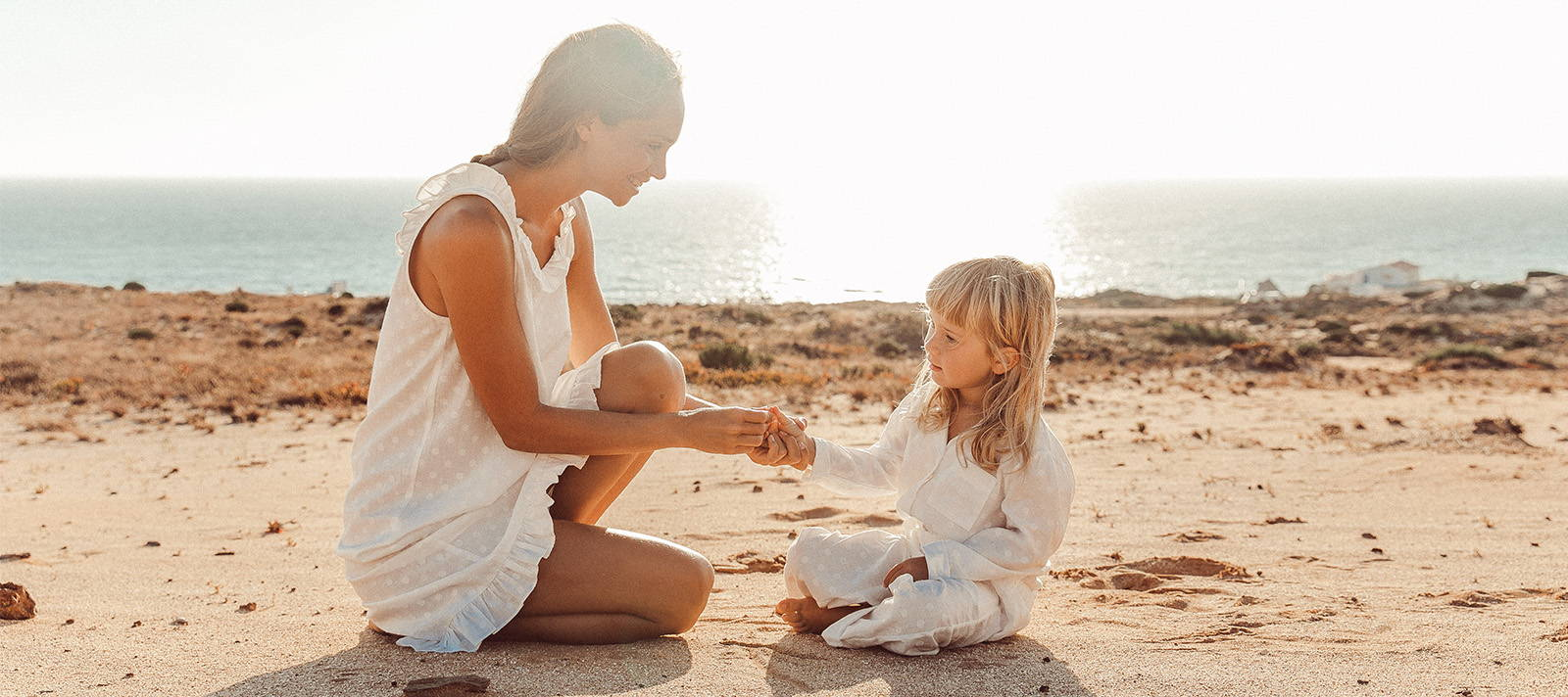 Mother and daughter sharing a secret on the beach matching in  a white cotton nightie and pyjamas
