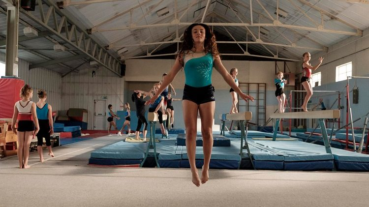 A young gymnast is airborne, mid-jump in a gymnastics hall.