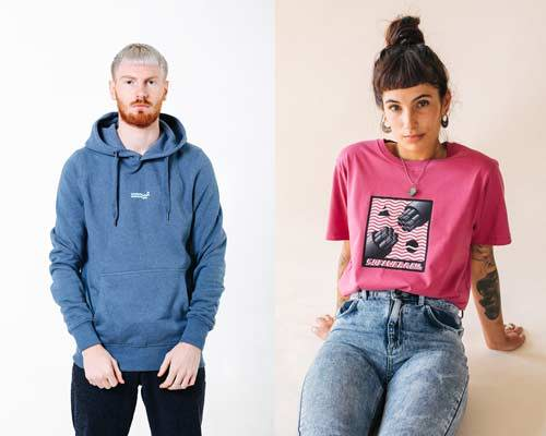 Man wearing washed out blue organic cotton hoodie with small Wawwa embroidered branding in the middle chest and woman wearing acid wash denim with an organic cotton bright pink t-shirt with a space inspired pink, white and black graphic illustration both from sustainable fashion brand Wawwa