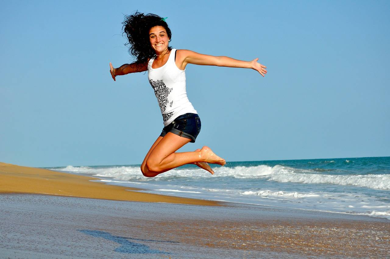 Girl jumping on the beach with energy
