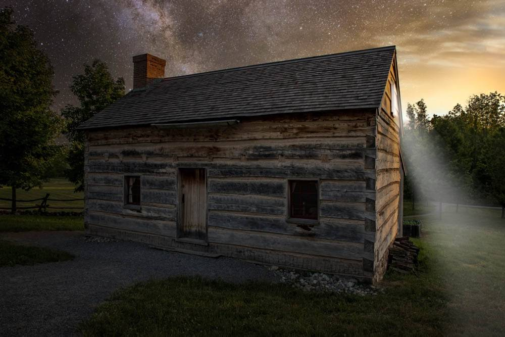 Photo of the Smith family cabin. The light of the angel Moroni shines from the upper window.
