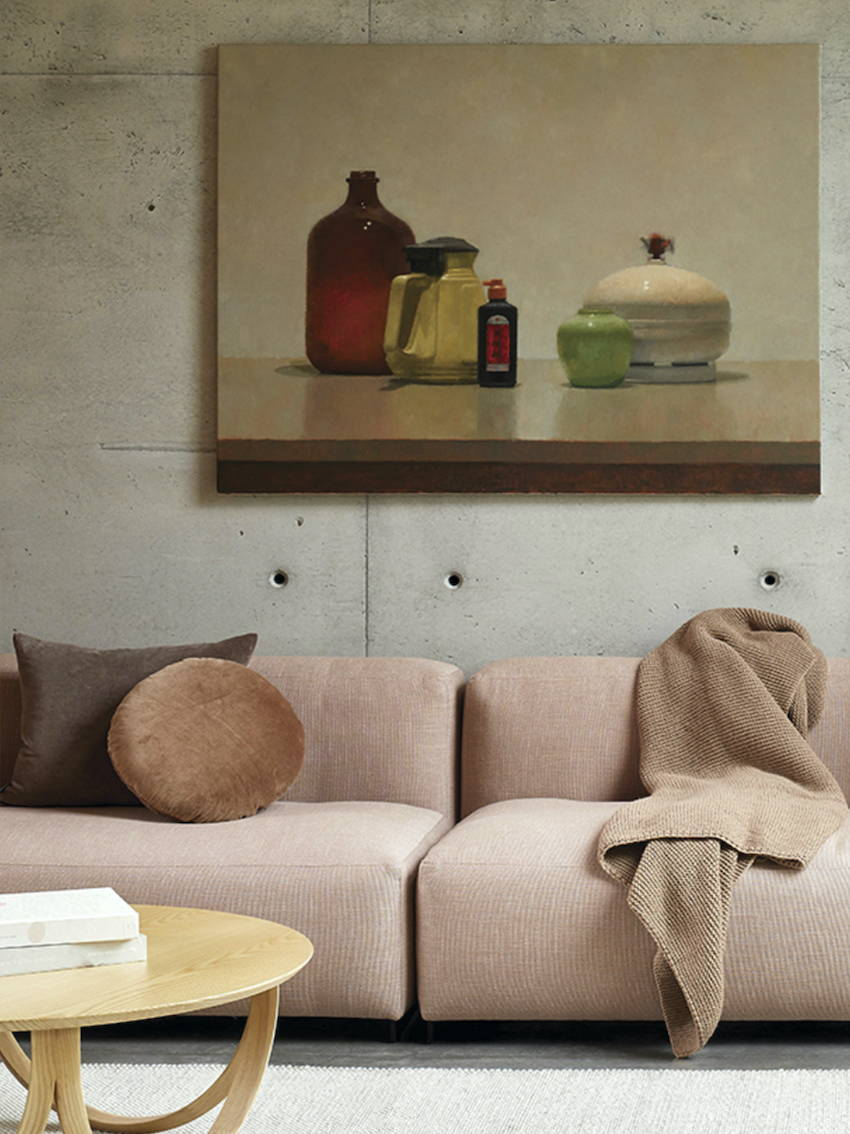 A lounge room setting with a pink sofa dressed with beautiful cushions and throws and a still life artwork on the wall.
