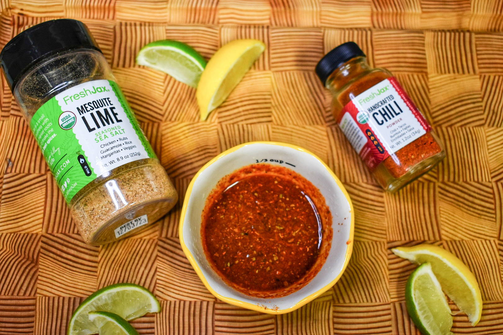 FreshJax Organic Mesquite Lime spice bottle and Handcrafted Chili spice bottle on cutting board with lemon, lime wedges and chili sauce