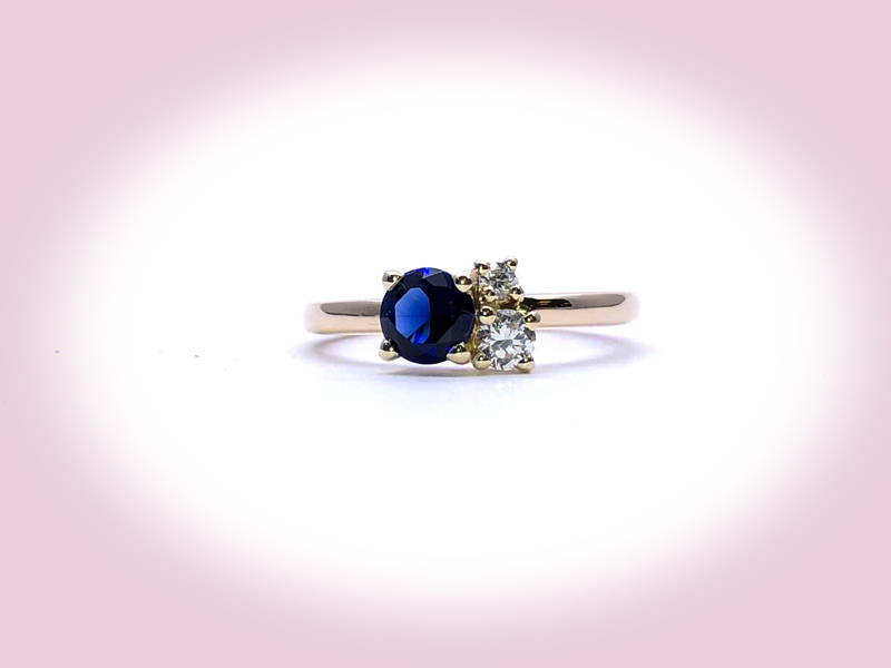 One sapphire and two diamonds on a fine yellow gold ring